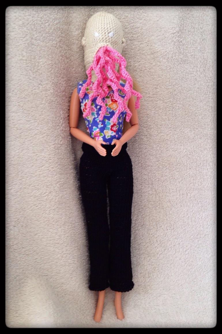 A Barbie doll wearing black pants.