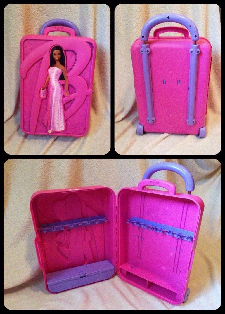 A pink Barbie rolling suitcase with a Barbie sticker on the front.