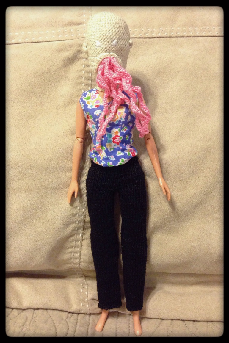 A picture of a Barbie doll wearing her Ood mask and Ood pants.