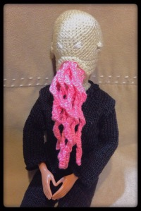 A Barbie doll wrarinf an Ood mask and outfit.