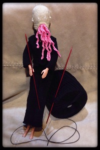 an Ood doll with yarn and knitting needles